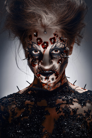 A creepy halloween makeup of a witch with a bloody peircing and cracked face paint.