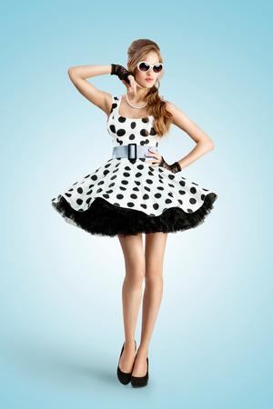 pin up vintage: Una foto d'epoca di una bella ragazza pin-up che indossa un abito e occhiali da sole a pois retrò.