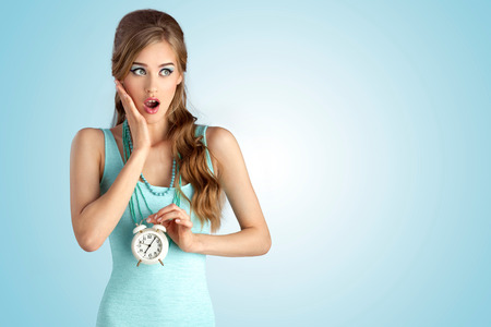 A conceptual photo of the ashamed girl with vintage clock in her hand. 免版税图像