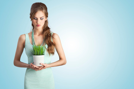 A beautiful sensual girl in white dress holding a flower pot of decorative lawn grass. photo