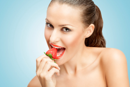 sexy naked girl: A creative portrait of a beautiful girl biting a red ripe strawberry sexually. Stock Photo