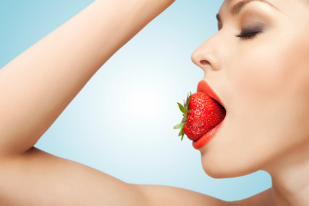 desnudo artistico: Un retrato de una mujer desnuda de sexy sosteniendo una fresa roja madura en su boca.