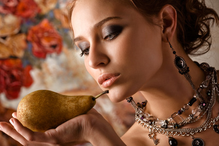 A close-up of a beautiful elegant woman holding a pear on her palm  photo