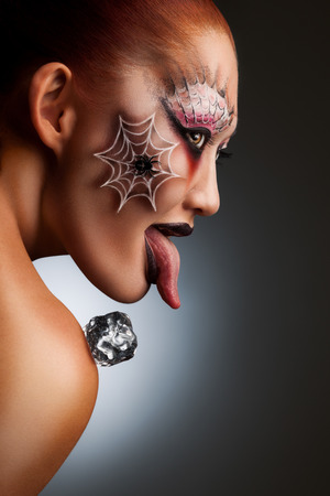 A portrait of a girl with halloween spider tattoo painted on her face as a scary mask with an ice cube on her shoulder  photo