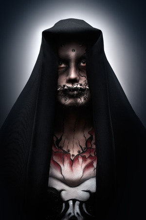 maul: A man covered with a hood in a creepy halloween costume of a monk with piercing and tattoo  Darth Maul
