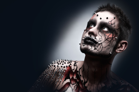 A creepy halloween makeup of a dark thoughtful moor with a peircing and scary body art