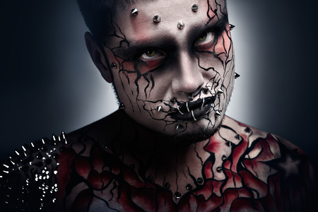 necromancer: A creepy portrait of a pierced halloween moor with bloody body art  Stock Photo
