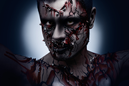 scary man: A creepy halloween concept of a dark angry moor with a peircing and bloody body art  Stock Photo