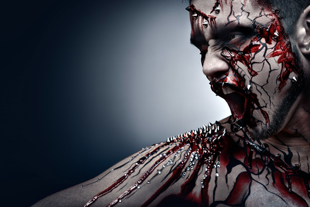 A creepy halloween concept of a screaming moor in pain with a piercing and bloody body art  photo