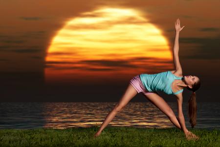 A sportive beautiful woman training yoga on the beach at dawn  photo