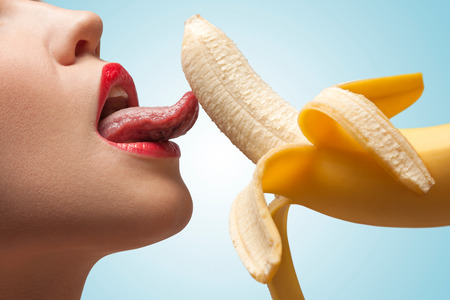 girls naked: A face of a hot girl that is licking a half-peeled yellow banana.