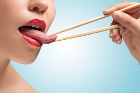 The photo of girl lower face with eating sticks hoding tongue. photo