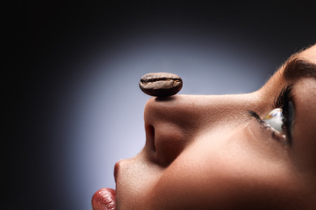 chocolate peak: A black roasted coffee bean on the nose of a beautiful girl smelling coffee and relaxing.
