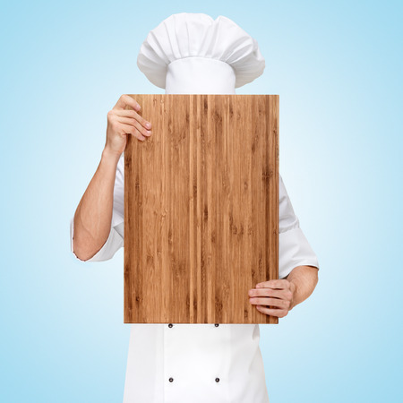 main board: Restaurant chef hiding behind a wooden chopping board for a business lunch menu with prices  Stock Photo