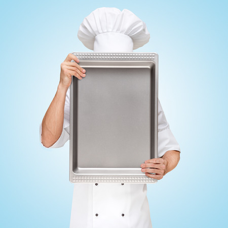 Restaurant chef hiding behind a baking pan for a business lunch menu with prices  photo