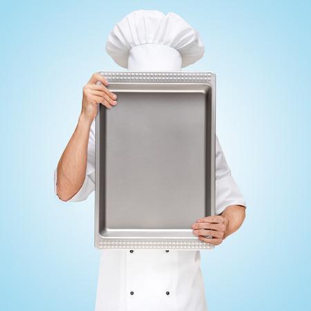 Restaurant chef verstopt achter een bakblik voor een zakelijke lunch menu met prijzen