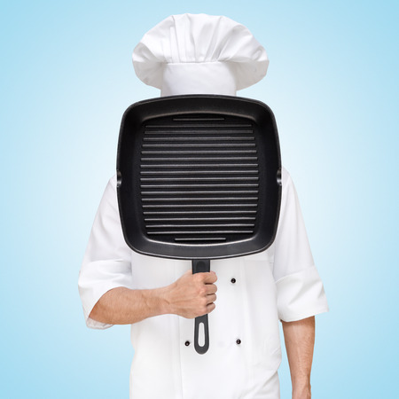 Restaurant chef hiding behind a grilling pan for a business lunch menu with prices