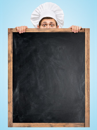Restaurant chef hiding behind a big empty chalkboard for a business lunch menu with prices  photo