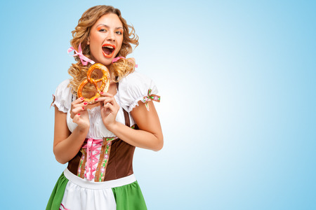 Young excited Oktoberfest woman wearing a traditional Bavarian dress dirndl holding a pretzel in hands on blue background. photo