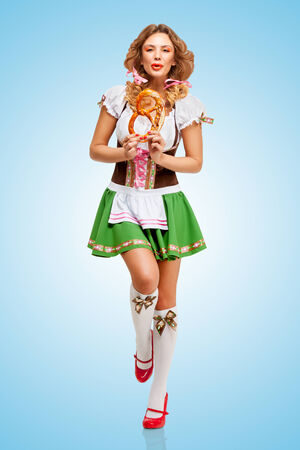 Young happy dancing Oktoberfest woman wearing a traditional Bavarian dress dirndl holding a pretzel in hands on blue background. photo