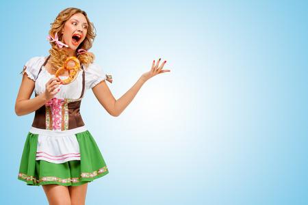 Junge sexy Oktoberfest Frau trägt ein traditionelles bayerisches Dirndl Kleid tanzen mit einer Brezel in der Hand auf blauem Hintergrund. Standard-Bild - 30286910