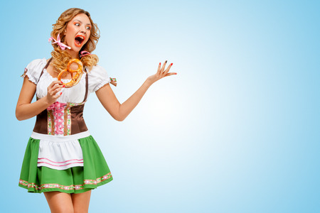 Young sexy Oktoberfest woman wearing a traditional Bavarian dress dirndl dancing with a pretzel in hands on blue background.
