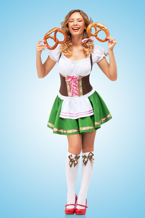 Young sexy Oktoberfest woman wearing a traditional Bavarian dress dirndl laughing happily and holding two pretzels in hands on blue background. photo