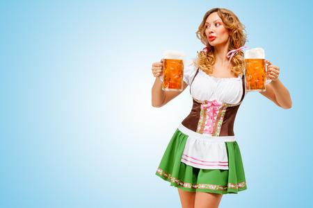 octoberfest: Mujer Oktoberfest sexy joven llevaba una tradicional dirndl vestido bávaros sirven dos tazas de cerveza sobre fondo azul.