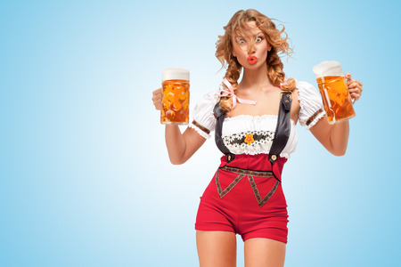 Young surprised sexy Swiss woman wearing red jumper shorts with suspenders in a form of a traditional dirndl, holding two beer mugs on blue background.