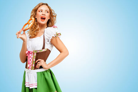 Young sexy Oktoberfest woman wearing a traditional Bavarian dress dirndl eating a pretzel on blue background. photo