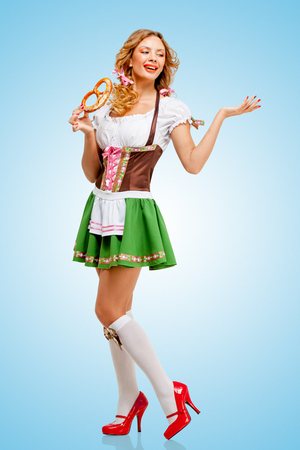 Young sexy Oktoberfest woman wearing a traditional Bavarian dress dirndl posing with a soft salty pretzel on blue background. photo