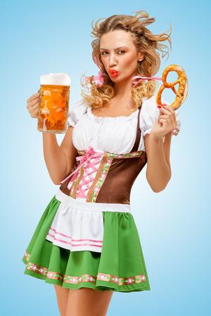 Junge sexy Oktoberfest Frau trägt einen traditionellen bayerischen Kleid Dirndl posiert mit einer Brezel und Bierkrug in der Hand auf blauem Hintergrund.
