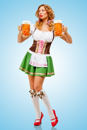 Young sexy Oktoberfest woman wearing a traditional Bavarian dress dirndl serving two beer mugs on blue background.