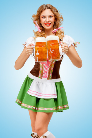 Young sexy Oktoberfest woman wearing a traditional Bavarian dress dirndl serving two beer mugs with happy smile on blue background