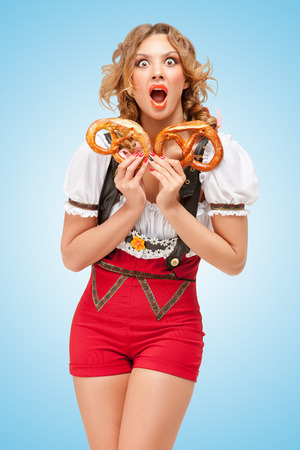 pretzels: Young sexy Swiss woman wearing red jumper shorts with suspenders in a form of a traditional dirndl, holding with hunger two pretzels on blue background