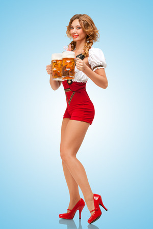 Young excited sexy Swiss woman wearing red jumper shorts with suspenders in a form of a traditional dirndl, serving two beer mugs on blue background  Stock Photo
