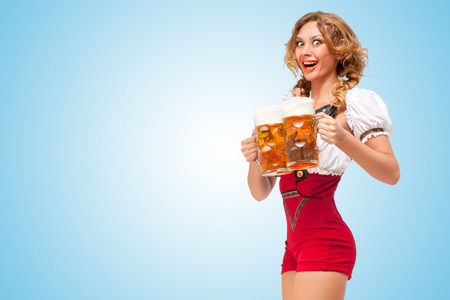 dirndl: Young excited sexy Swiss woman wearing red jumper shorts with suspenders in a form of a traditional dirndl, serving two beer mugs on blue background  Stock Photo