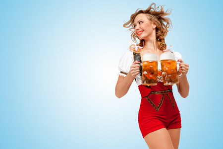 Young smiling sexy Swiss woman wearing red jumper shorts with suspenders in a form of a traditional dirndl, holding two beer mugs and looking aside on blue background