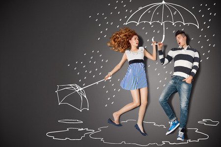 couple dating: Happy valentines love story concept of a romantic couple in the rain against chalk drawings background.