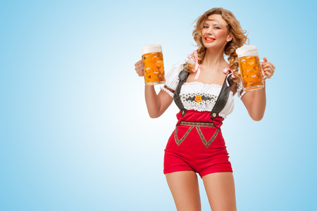 Young smiling sexy Swiss woman wearing red jumper shorts with suspenders in a form of a traditional dirndl, holding two beer mugs on blue background.