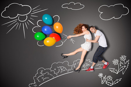 Happy valentines love story concept of a romantic couple holding balloons blowing with the wind against chalk drawings background  photo