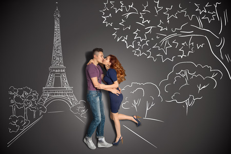 Happy valentines love story concept of a romantic couple in Paris kissing under the Eiffel Tower against chalk drawings background  Stock Photo