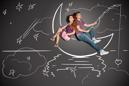 Happy valentines love story concept of a romantic couple fishing on a moon with a heart on a hook against chalk drawings background