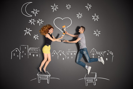 Happy valentines love story concept of a romantic couple standing on a stool and painting a heart in the night sky against chalk drawings background
