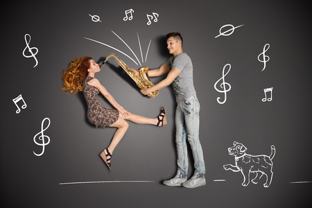 love story: Happy valentines love story concept of a romantic couple against chalk drawings background  Female playing the sax for her boyfriend