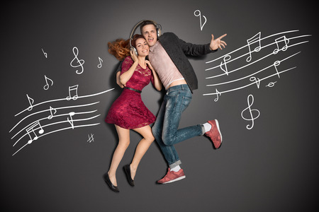 Happy valentines love story concept of a romantic couple sharing headphones and listening to the music against chalk drawings background Stok Fotoğraf - 30611335