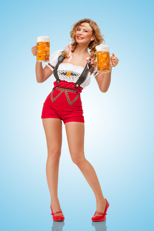 swiss culture: Young smiling sexy Swiss woman wearing red jumper shorts with suspenders in a form of a traditional dirndl, holding two beer mugs on blue background