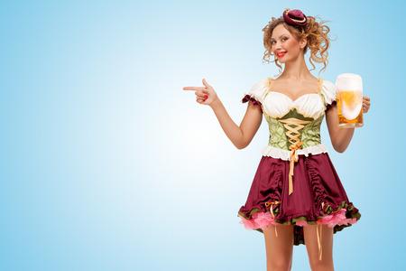 Junge sexy Oktoberfest Kellnerin trägt einen traditionellen bayerischen Kleid Dirndl hält einen Bierkrug, und zeigen beiseite auf blauem Hintergrund