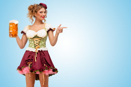dirndl: Young sexy Oktoberfest waitress wearing a traditional Bavarian dress dirndl holding a beer mug, and pointing aside on blue background