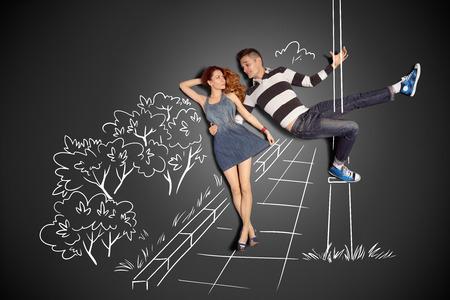 Happy valentines aiment concept de l'histoire d'un couple romantique contre dessins à la craie fond. Homme pole dancing sur un lampadaire tout en marchant avec sa petite amie. Banque d'images - 30644834